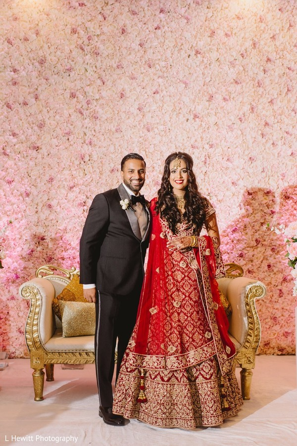 Indian couple posing on wedding reception stage.