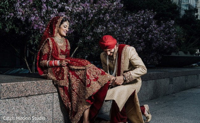 Indian bride getting her shoes on by groom.