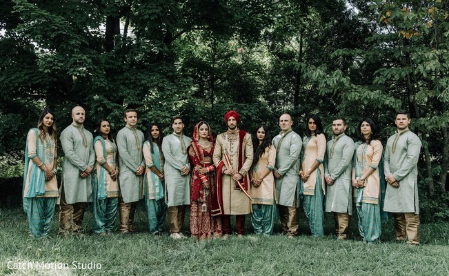 Indian couple with bridesmaids and groomsmen posing outdoors.