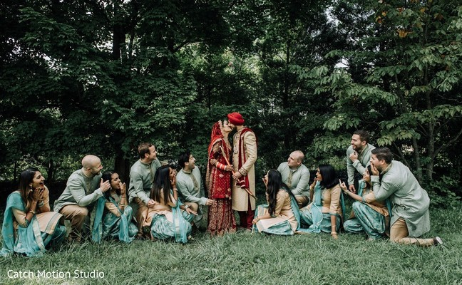 Indian couple posing with bridesmaids and groomsmen photo session.