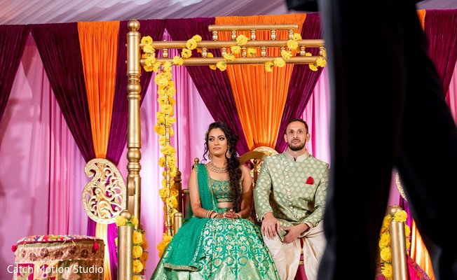 Indian bride and groom at sangeet swing decorated seat.