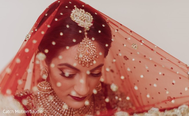 Indian bridal with her red ghoonghat and golden tikka.