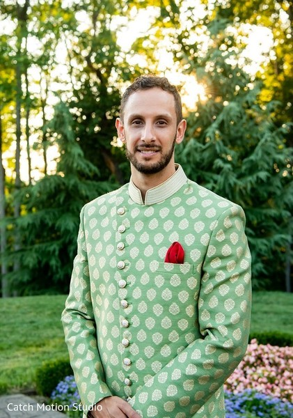 Indian groom posing outdoors on sangeet outfit.