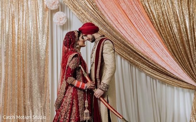 Indian bride and groom on their golden and red ceremony outfits.