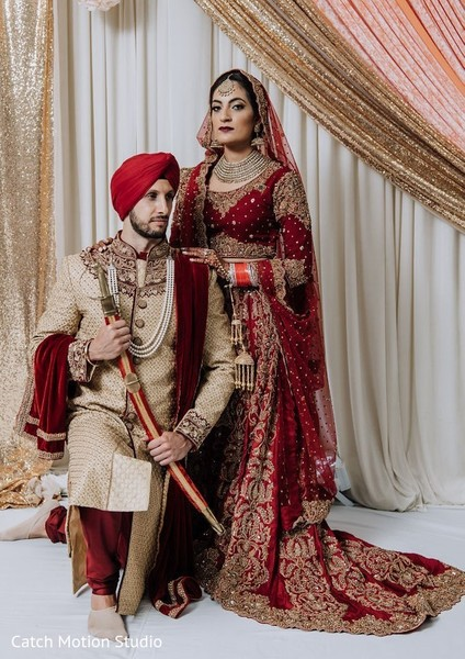 Indian bride and groom posing at ceremony mandap.