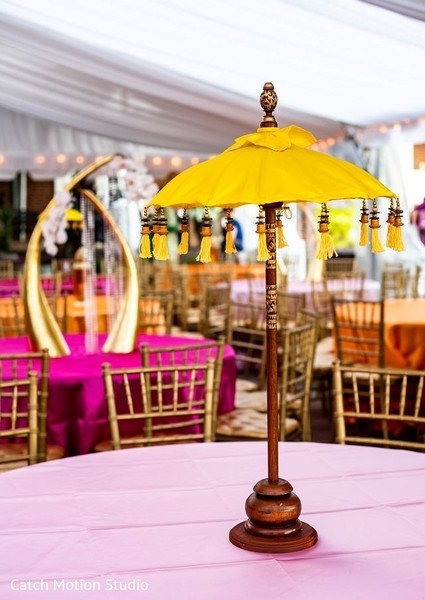 Sangeet table centerpiece yellow and wood umbrella decoration.