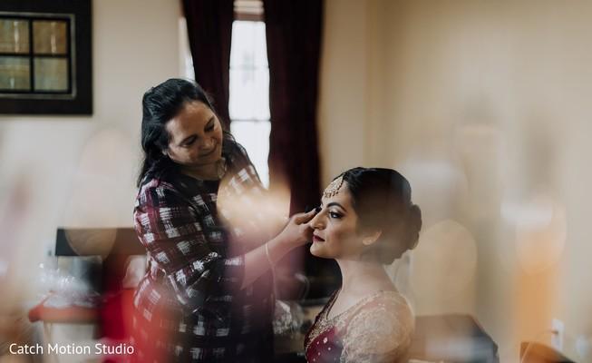 Indian bride getting her wedding ceremony makeup.