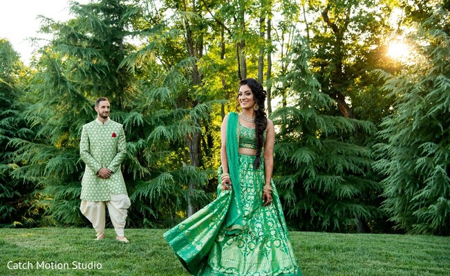 Indian bride and groom posing out in garden.