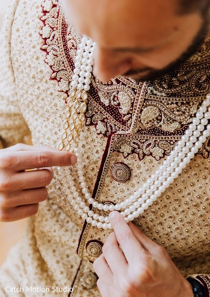 Indian groom putting his wedding ceremony necklace.