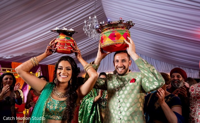 Indian bride and groom holding decorated pots.