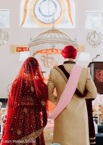 Indian couple standing in front of sikh ceremony altar.