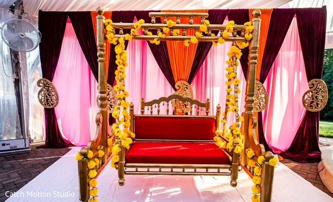 Red and golden sangeet swing seat with yellow flowers.