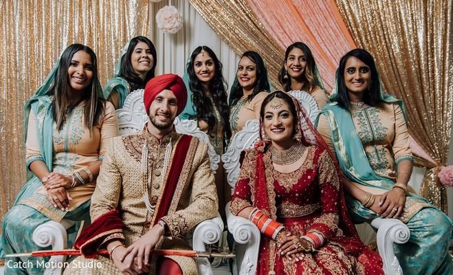 Indian couple with bridesmaids posing at mandap.