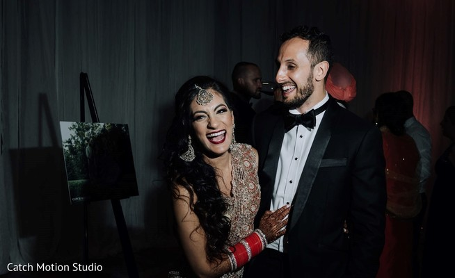 Indian bride and groom smiling at reception party.