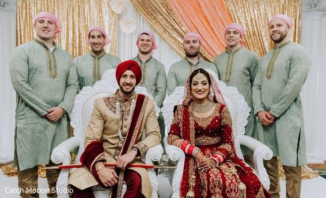 Indian couple with groomsmen posing at mandap.