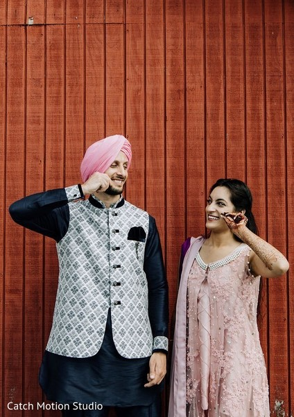 Indian bride and groom posing outdoor on pre-wedding outfits.