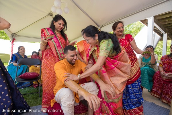Indian relatives applying tumeric paste to the Indian groom