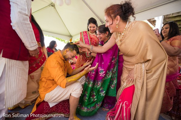 Indian relatives applying tumeric paste on the Indian groom's head