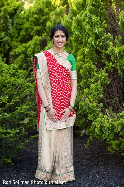 Indian bride posing in front of the bushes