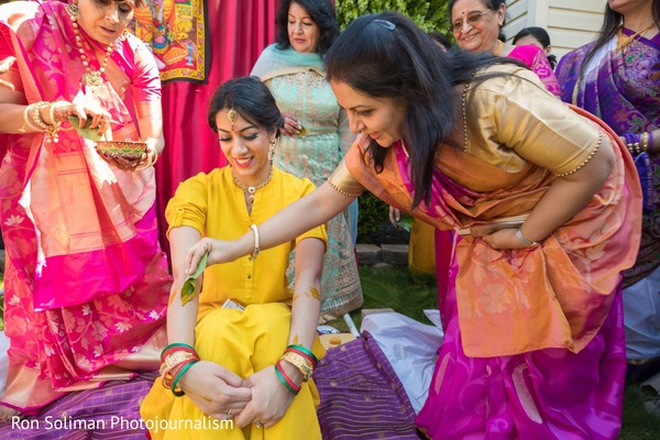 Indian relative s applying tumeric paste to the Indian bride's arms