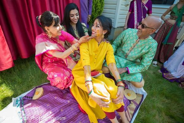Indian relative applying tumeric paste to Maharani's face