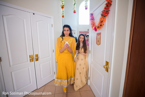 Indian bride walking through a hall followed by Indian relatives