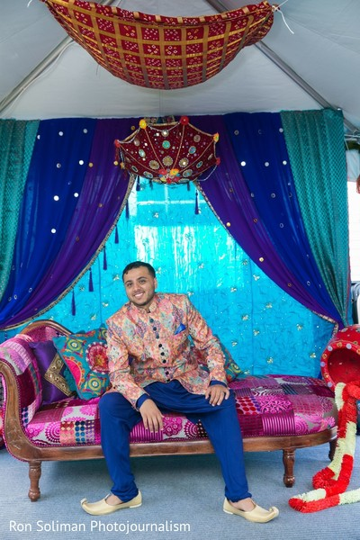 Indian groom sitting on a couch surrounded by decorations