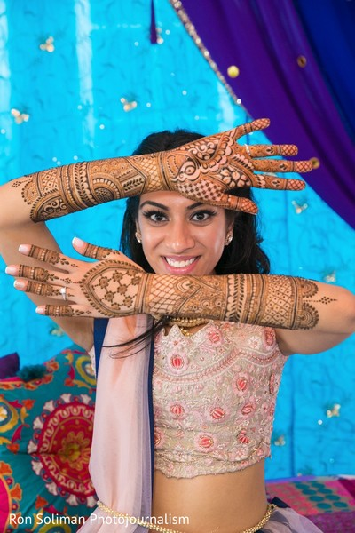 Maharani striking a pose that shows off the mehndi on her arms