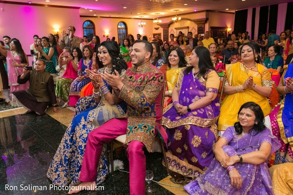 Indian couple, Indian family and guests clap to a performance