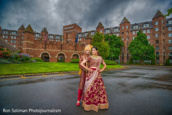Indian couple in their wedding attires posing in front of the venue