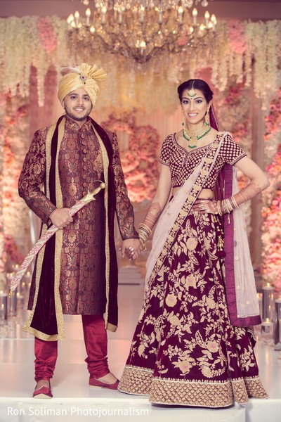 Indian couple in their wedding attires, holding hands