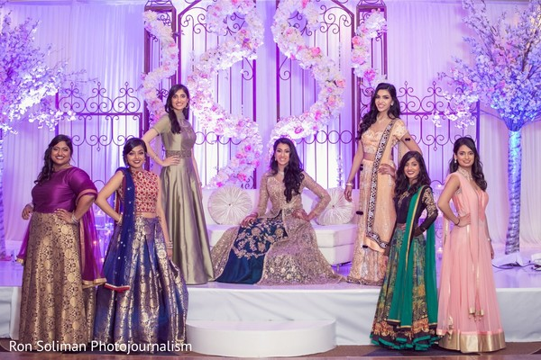Indian bride and her Indian bridesmaids posing on a decorated stage