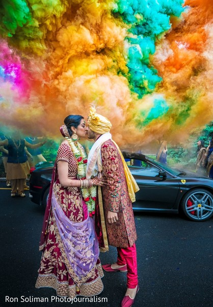 Indian couple kissing in front of an explosion of colors