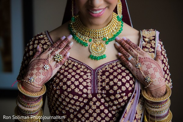 Indian bride showing off her jewelry and henna stained hands