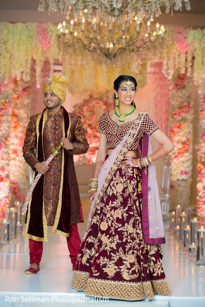 Indian couple in their red wedding attires posing on a decorated hall