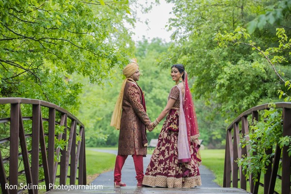 Indian couple holding hands at the other side of the bridge
