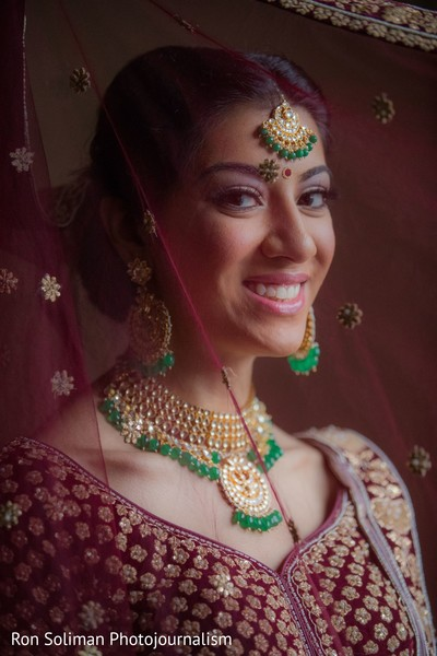 Indian bride smiling behind a veil
