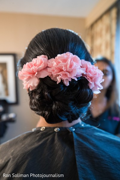 Indian bridal ping carnation pink flowers on hairstyle.