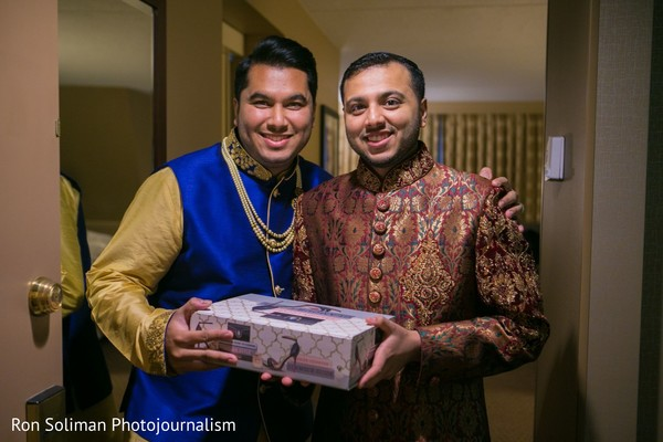 Indian groom getting a present from best man.