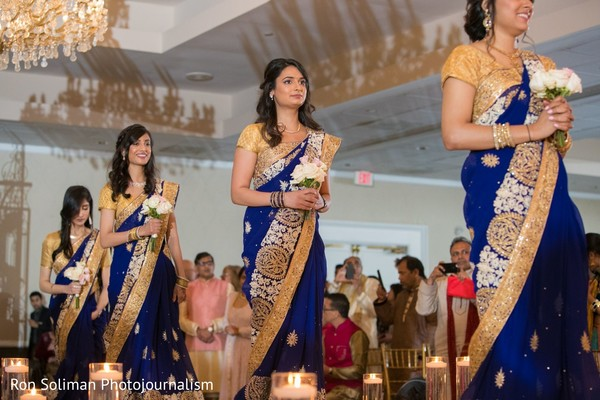 Indian bridesmaids on the aisle on their golden and royal blue sari.