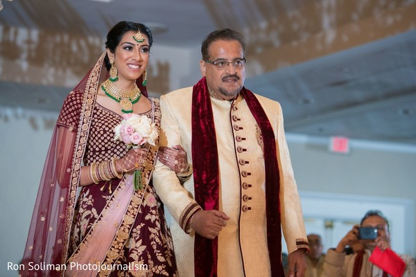 Joyful Indian bride next to her parent at wedding ceremony.