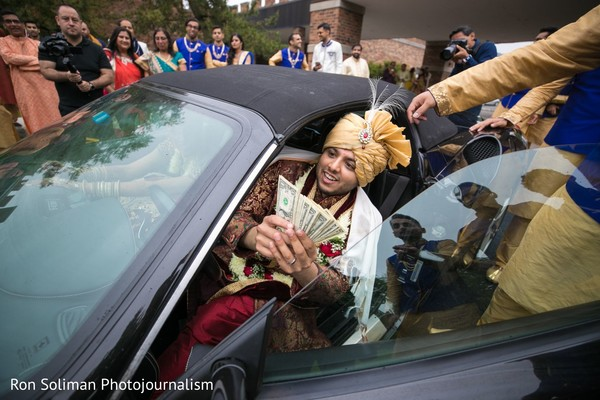 Indian groom giving money to bridesmaids game.