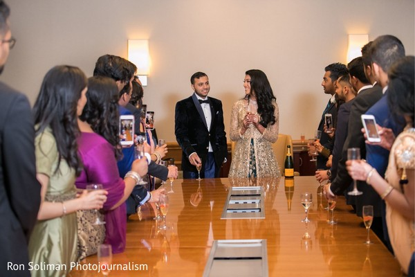 Indian bridesmaids and groomsmen having cheers with couple.