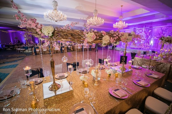 Golden, pink and white indian wedding reception table decoration.