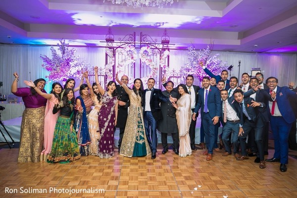 Indian couple at reception stage with wedding guests capture.
