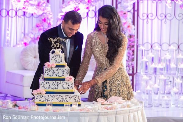 Maharani and raja cutting reception wedding cake.