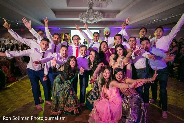 Indian couple with bridesmaids and groomsmen at reception capture.