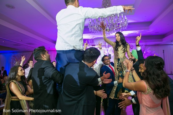 Indian couple being lifted at wedding reception celebration.