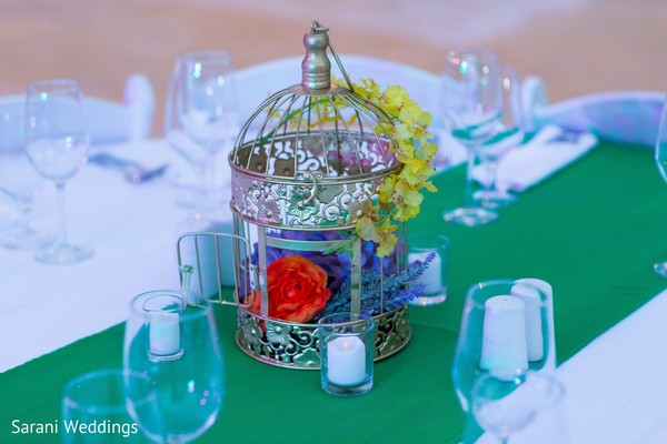 Sangeet Indian pre-wedding table birdcage and flowers decorations.