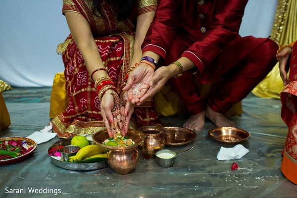 Indian couple poussin rice into sacred tray.